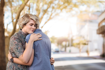 Loving young lesbian couple standing outside hugging each other
