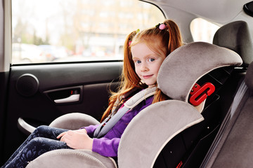 portrait of a cute red-haired little girl sitting in a child car seat.