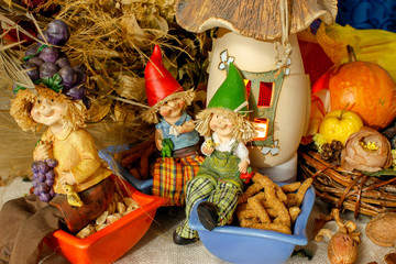 Beautiful composition iwith figurines of child's, snacks, dry leaves, walnuts and rustic decoration. Candle light, nice holiday decoration.
