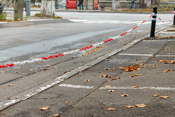 white and red plastic chain tied to a iron pole in the parking lot with blurred city street in background.