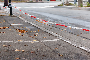 white and red plastic chain tied to a iron pole in the parking lot