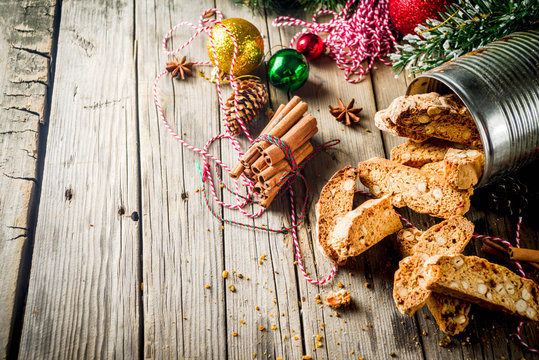 Traditional Christmas pastries, Italian homemade double-baked biscotti or cantuccini cake, with nuts and dried fruits. with xmas decorations and fir branches, old wooden background copy space