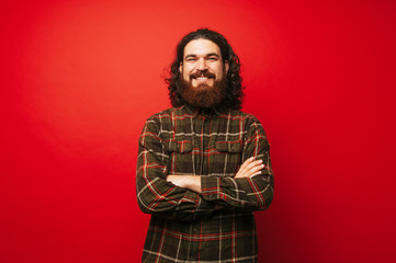 Portrait of cheerful bearded hipster man with crossed arms over red background