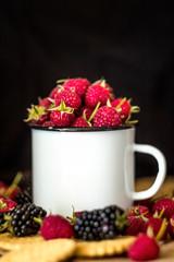 Metal white mug with raspberries, blackberries and crackers on a dark background