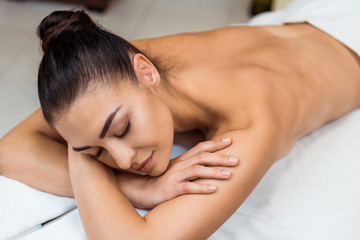 high angle view of attractive young woman with closed eyes lying on massage table