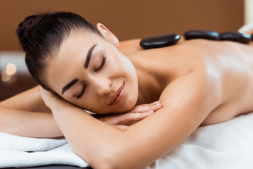 smiling young woman with closed eyes enjoying hot stone massage in spa salon
