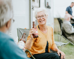 Happy senior woman with a bottle of beer