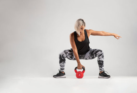 Beautiful female Middle Eastern fitness athlete  with  modern funky hairstyle and wearing sports clothing about to do a kettle bell lifting exercise from a squatting position