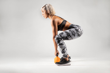 Side view of beautiful female Middle Eastern fitness athlete  with  modern funky hairstyle and wearing sports clothing about to do a kettle bell lifting exercise from a squatting position