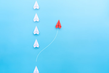 Group of white paper plane in one direction and one red paper plane pointing in different way on blue background. Business concept for new ideas, creativity, innovation and solution.