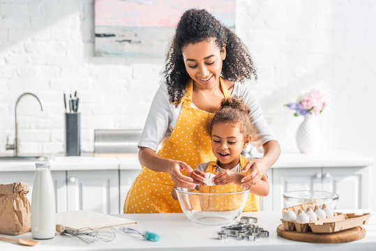 smiling african american mother helping daughter breaking egg for preparing dough in kitchen