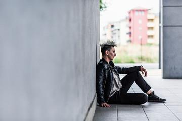 Punk woman sitting near wall