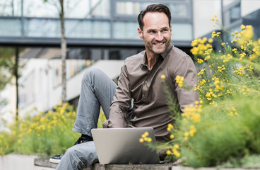 Portrait of smiling businessman working with laptop outdoors