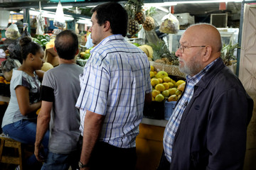 Benito Urrea waits in line to pay for his groceries at a fruit and vegetables stall at a municipal market in Caracas