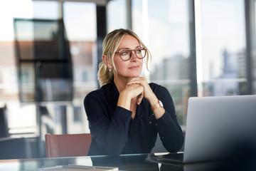 Thoughtful businesswoman wearing eyeglasses sitting in office