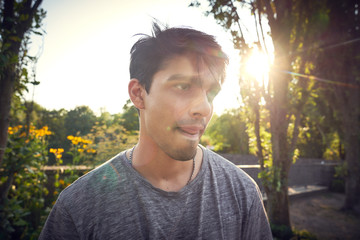 Portrait of a young man in a park at sunset