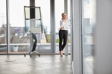 Successful businessman standing in office, looking out of window