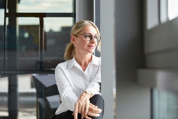 Serene businesswoman sitting on ground, looking out of window