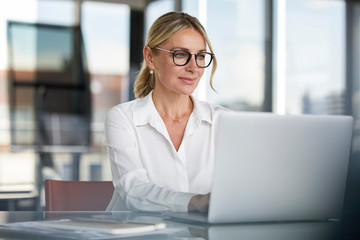 Businesswoman working in office, using laptop