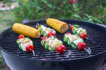 Grilled vegetarian grill skewers, tomato, sheep cheese and zucchini slices, corn cobs on grill