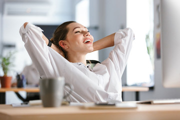 Happy young woman dressed in shirt sitting at her workplace Wall mural