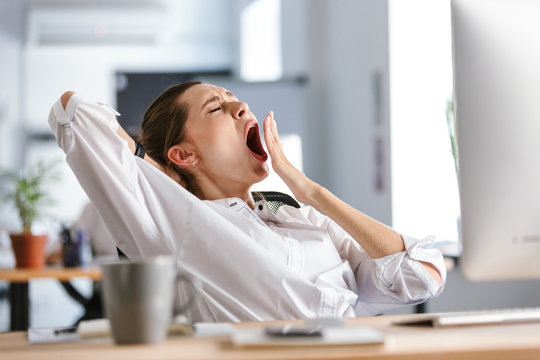 Sleepy young woman dressed in shirt sitting at her workplace