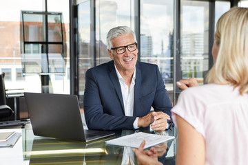 Businessman snd woman sitting in office, discussing project