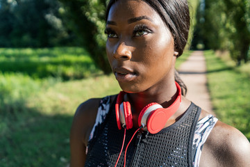 Young athlete in nature, listening music with headphones, holding smartphone