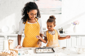 african american mother and daughter looking at cookies on tray in kitchen