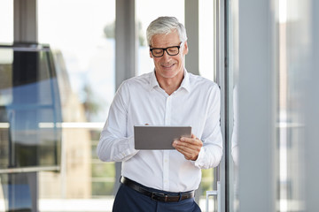 Businessman leaning on window, using digital tablet