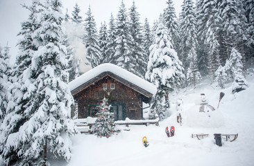 Austria, Altenmarkt-Zauchensee, snowman, sledges and Christmas tree at wooden house in snow