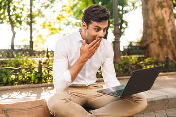 Cheerful young businessman sitting outdoors