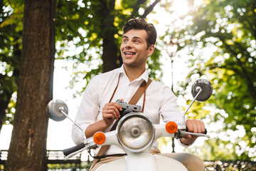 Happy young businessman riding on a motorbike