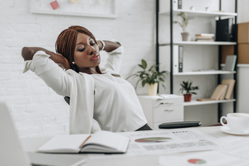 beautiful african american adult businesswoman in white formal wear with hands behind head sitting at desk and relaxing at modern office
