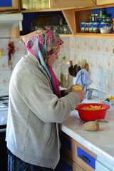 Senior woman peels potatoes in the kitchen. Turkish old woman preparing potatoes for frying.