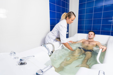The young man is the procedure in the whirlpool hydrobath