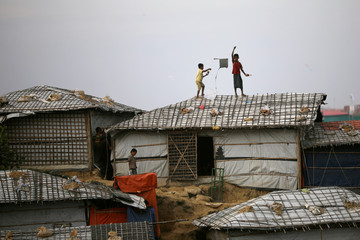 Rohingya refugee children fly kites on top of their shelter at Balikhali camp in Cox's Bazar