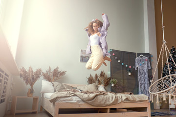 funny happy girl jumping and having fun in bed