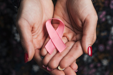 young woman with a pink ribbon in her hands.
