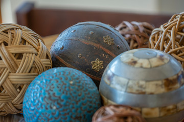 Detailed view of decorative balls, wicker, wood, minerals and plastics, with relief and painted