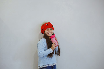 A little girl with a thermos in her hand.