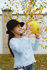 A little girl playing with the ball.