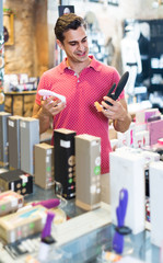 Adult man buyer choosing different sexy toys in the sex shop