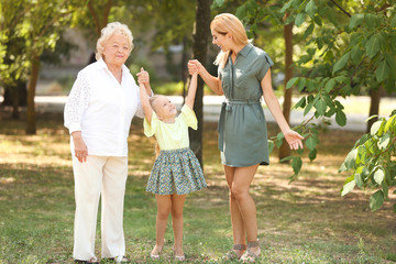 Woman with daughter and elderly mother in park on sunny day
