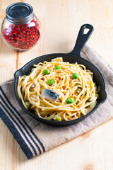 Food concept spaghetti creamy white sauce in cast-iron skillet pan on wood background