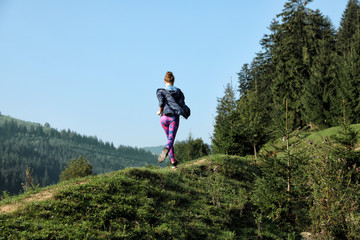 Young woman running on mountain trail in summer