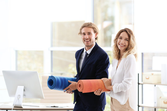 Young businessman and businesswoman holding yoga mats in office. Gym after work