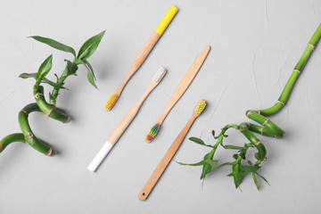 Flat lay composition with bamboo toothbrushes on grey background