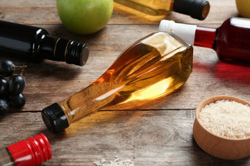 Bottles with different kinds of vinegar and ingredients on wooden table
