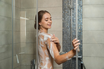 Young woman covered with soap foam taking shower in bathroom